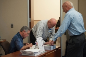"Juan Garcia, co-author of the ""Drillers Knowledge Book"", left, and Ron Sweatman, author of ""Well Cementing Operations"", sign their respective books for Tech Forum attendees."